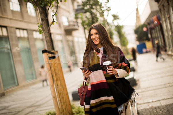 Woman standing outside, drinking coffee to go and holding a mobi Stock photo © boggy