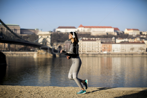 Young female athlete running on the waterfront in Budapest, Hung Stock photo © boggy
