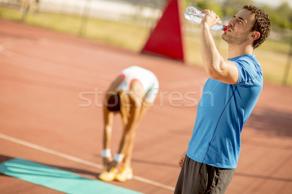 Sporty man drinking water while young woman doing exercise in th Stock photo © boggy