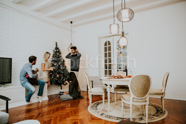 Young people decorate fir-tree for holidays of Christmas and New Stock photo © boggy