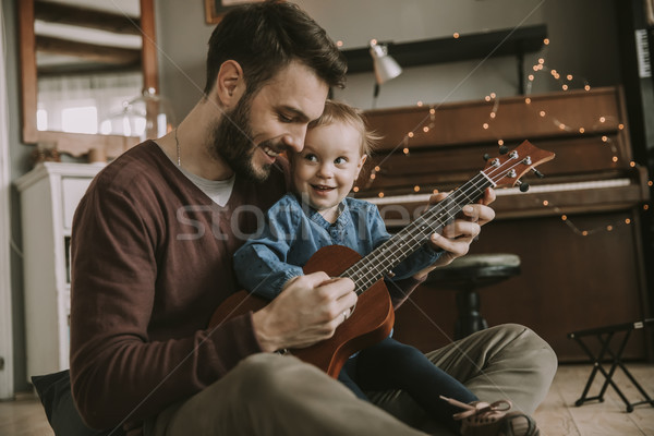 Father teaching daughter to play guitar at home Stock photo © boggy
