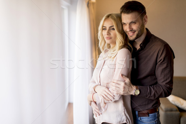 Loving couple by window in the room Stock photo © boggy