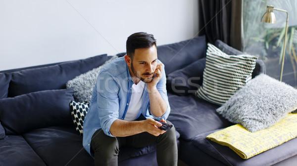 Fiatalember távirányító kanapé szoba ház televízió Stock fotó © boggy