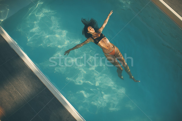 Young woman floating in the pool Stock photo © boggy