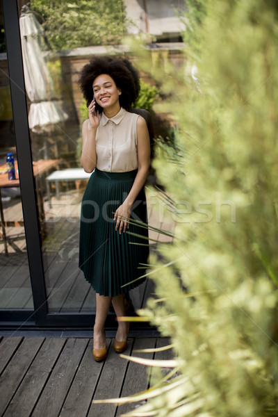 Curly hair cheerful woman uses a phone in while standing in the  Stock photo © boggy