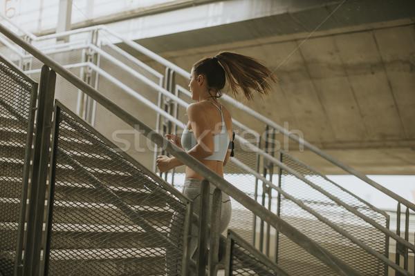 Jonge vrouw lopen alleen omhoog trap outdoor Stockfoto © boggy