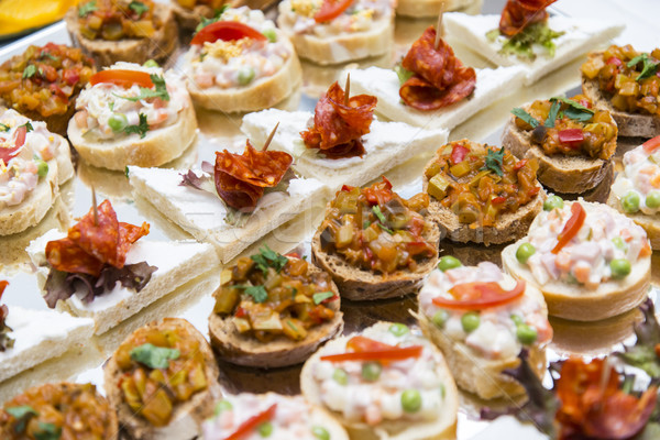 Colorful canape with vegetables and sausage on a slate plate Stock photo © boggy