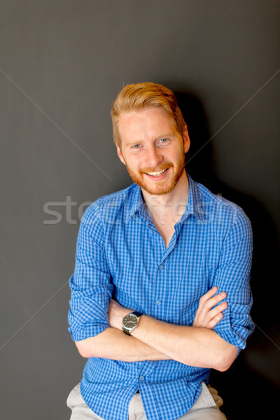 Portrait of ginger young man against wall Stock photo © boggy