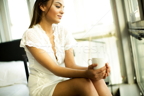 Young woman drinking coffee and dreaming on a chair by the windo Stock photo © boggy