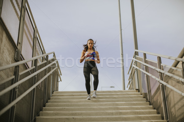 Jonge vrouw lopen alleen beneden trap outdoor Stockfoto © boggy