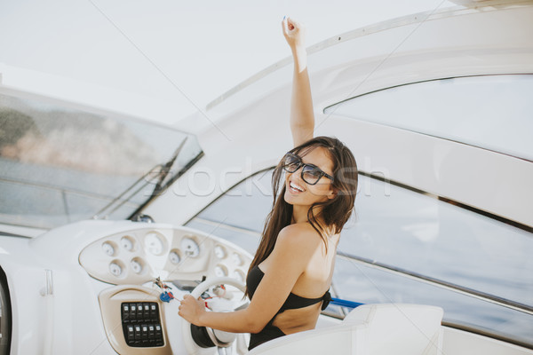 Young attractive woman drives a  yacht at sea Stock photo © boggy