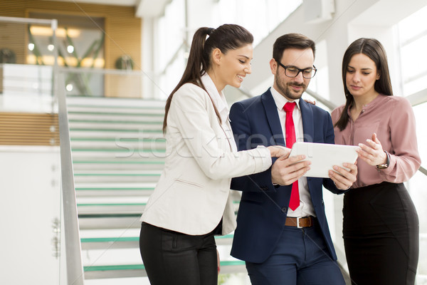 Smiling business team working on tablet pcs Stock photo © boggy