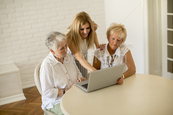 Happy women of three generations using laptop in the room at hom Stock photo © boggy