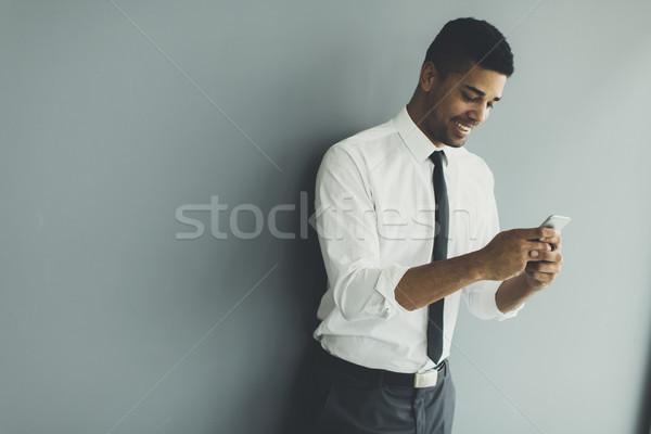 Yakışıklı genç siyah adam cep telefonu ofis hareketli Stok fotoğraf © boggy