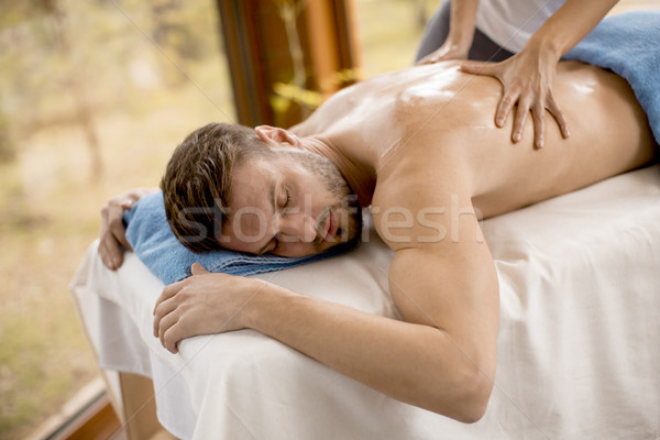 Young man having massage in the spa Stock photo © boggy