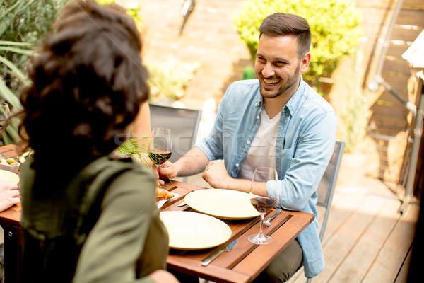 Fiatal pér ül asztal udvar fa asztal nő Stock fotó © boggy
