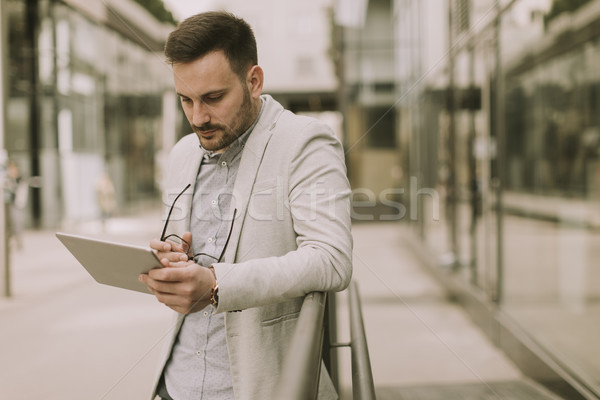Young businessman with digital tablet by the office building Stock photo © boggy