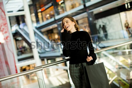 Young woman in shopping mall talking over mobile phone Stock photo © boggy