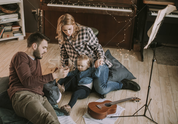 Happy young family playing on the floor Stock photo © boggy