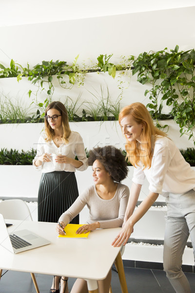 Three young businesswomen in the office Stock photo © boggy