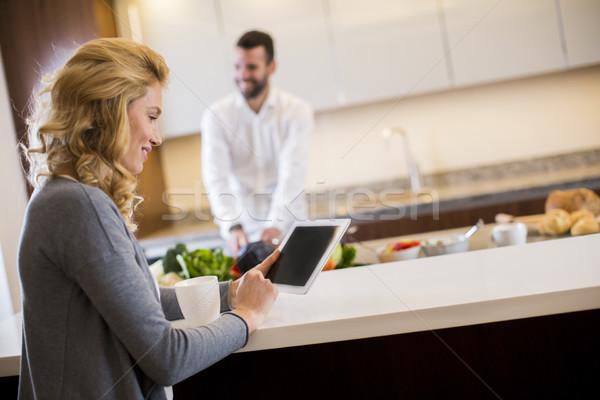 Nő tabletta konyhaasztal férfi ételt készít fiatal nő Stock fotó © boggy