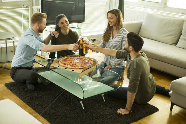 Young people eating pizza and drinking cider in the room Stock photo © boggy