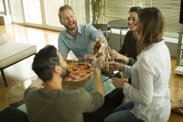 Young people eating pizza and drinking cider in the modern inter Stock photo © boggy