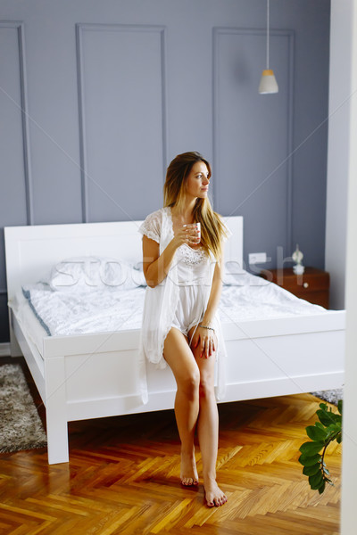 Woman drink a glass of water at morning after waking up Stock photo © boggy