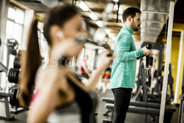 Young couple exercise bodybuilding exercises in the gym Stock photo © boggy