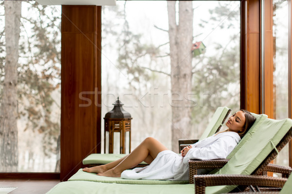 Stock photo: Pretty young woman relaxing on the deckchair by the swimming poo