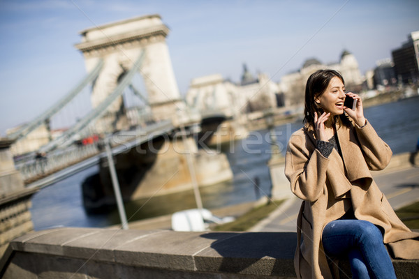 Young woman using mobile phone with Chain bridge at background i Stock photo © boggy