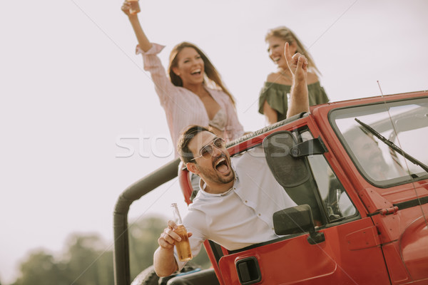 Happy friends having fun in convertible car at vacation Stock photo © boggy