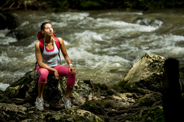 Young woman hiker rests next to the forest river Stock photo © boggy