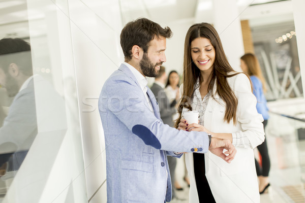 Young business man shows a watch to a businesswoman who drinking Stock photo © boggy