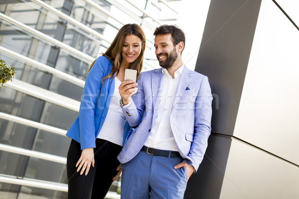Young couple with mobile phone in front of office building Stock photo © boggy