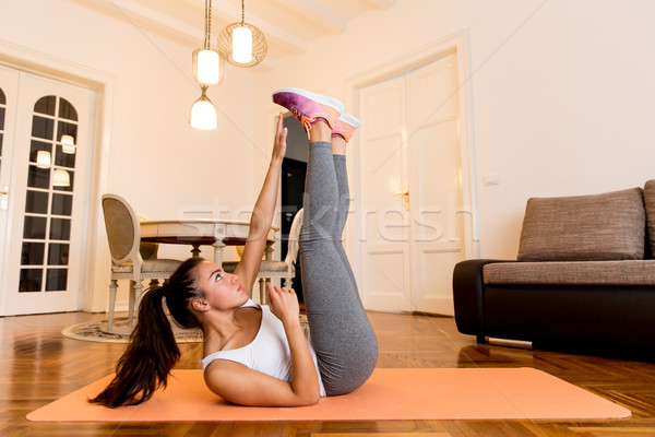 Young woman doing abs exercise in the room Stock photo © boggy