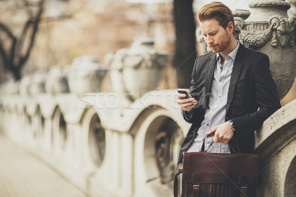 Young redhair businessman with mobile phone on a street Stock photo © boggy