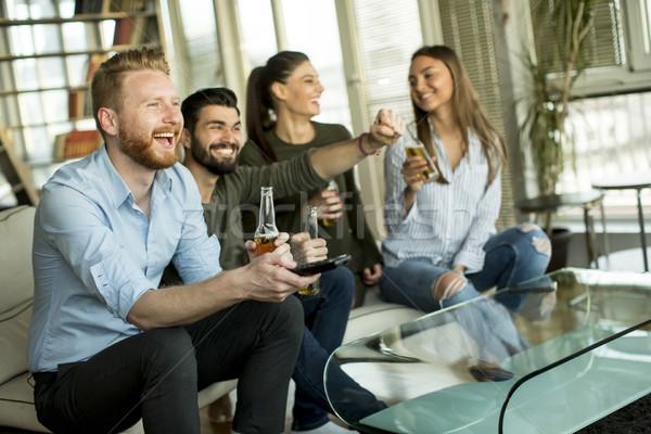 Groep jonge vrienden naar tv drinken Stockfoto © boggy