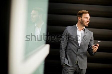 бизнесмен мобильного телефона глядя Смотреть Финансовый район бизнеса Сток-фото © boggy