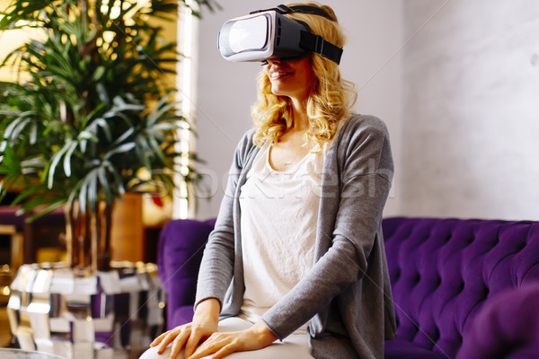 Woman wearing virtual reality goggles in the room Stock photo © boggy