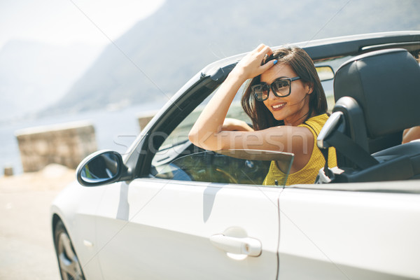 Pretty young woman in white cabriolet car Stock photo © boggy