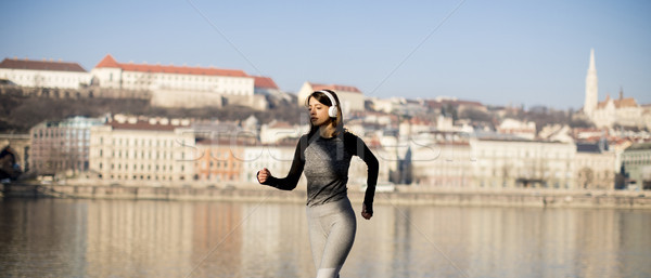 Woman in sportswear running on Danube river promenade in Budapes Stock photo © boggy