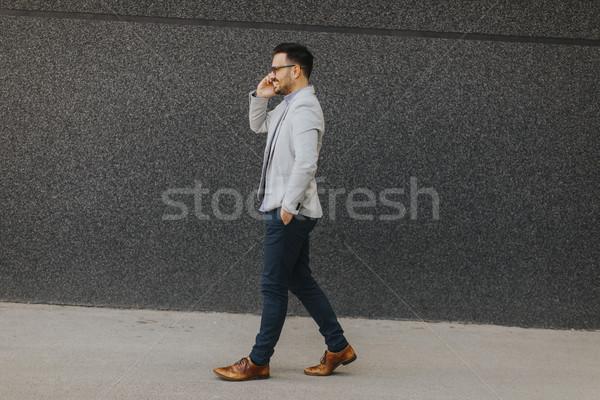 молодым человеком ходьбе говорить мобильного телефона Открытый стены Сток-фото © boggy