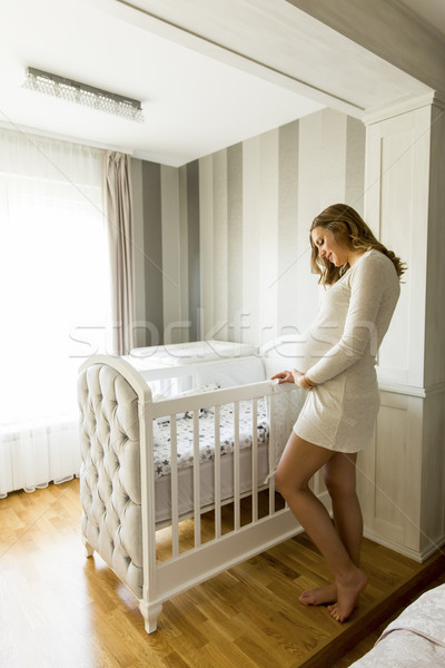 Pregnant woman setting up baby crib smiling Stock photo © boggy