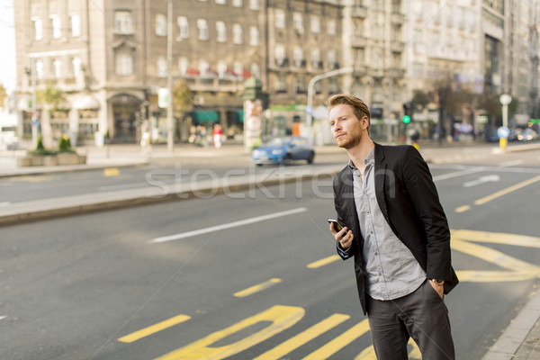 Young man on the street with mobile phone Stock photo © boggy