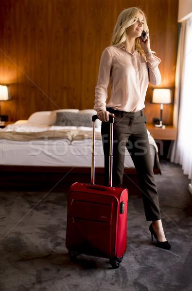молодые деловая женщина номер в отеле красный чемодан Сток-фото © boggy