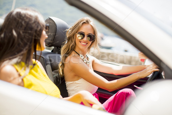 Stock photo: Young women in white cabriolet car driving everywhere and lookin
