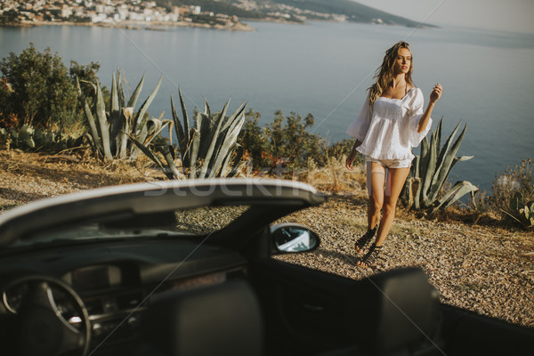Pretty young woman by the white cabriolet car Stock photo © boggy