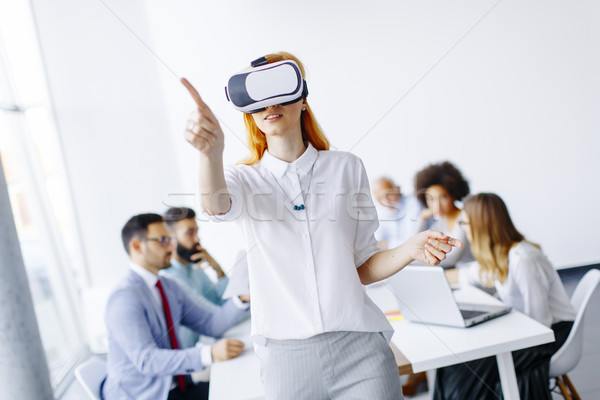 Excited businesswoman in virtual reality glasses trying to touch Stock photo © boggy