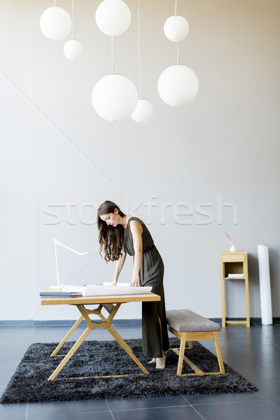 Stock photo: Young woman works on a project in a modern room